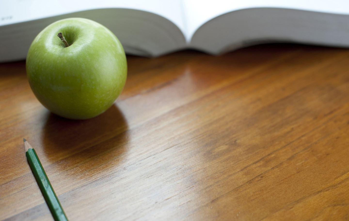 fresh green apple on wood desk with a textbook