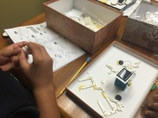 SLP 2016 student(s) work with gears and parts for robotics class with Mrs. Rosales; photo release on file